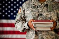 Military member holding textbooks in front of American flag