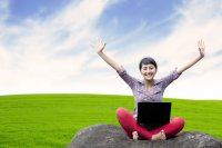 Young woman with laptop outside with arms raised