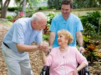 Caregiver with older couple out in nature