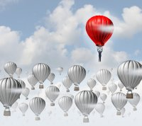A red hot air balloon rising above the others