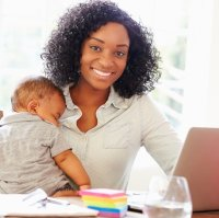 Mother holding baby while doing schoolwork
