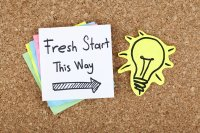 """Bulletin board with sticky note that reads """"Fresh start this way"""""""