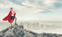 Individual in super hero cap standing on top of a mountain