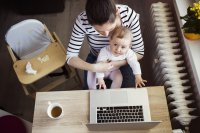 Mother with young child at laptop