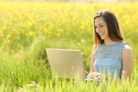 Young woman working outside on laptop
