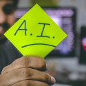 """Business professional holding sticky note with Artificial Intelligence """"AI"""" written on it"""