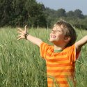 Young child in a field with arms oustretched in joy