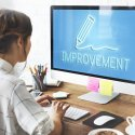 "Woman in front of computer with ""improvement"" written on the screen"