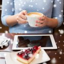 Woman with coffee at laptop with snow falling