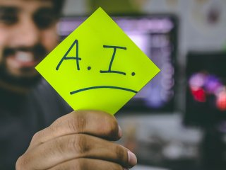 "Business professional holding sticky note with Artificial Intelligence ""AI"" written on it"