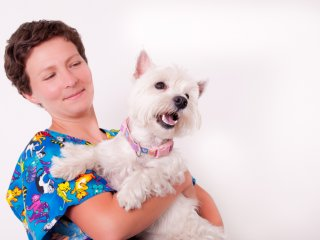 Vet assistant with cute dog in her arms