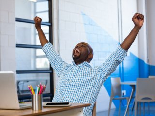 Attractive man with arms raised in success in front of laptop