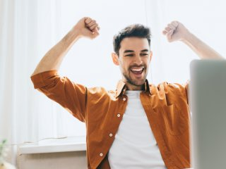 Man with arms upraised in sign of success