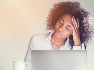Stressed young female professional at laptop